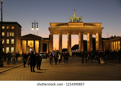 Berlin, Germany - October 2018: Evening view of Pariser Platz (Square) in Berlin city center and people in front of the illuminated Brandenburg Gate (Brandenburger Tor) with the Quadriga after sunset