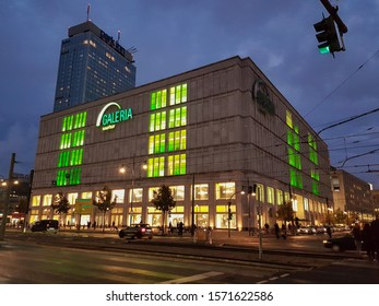 Berlin, Germany, October 2019: Galeria kaufhof Store. Evening, shop Windows and sign glow green. Behind the store building - Park Inn hotel