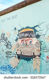 "Berlin, Germany - October 26, 2013: the murial titled ""Test the Rest"" by Birgit Kinder on a remnant of the Berlin Wall, East Side Gallery, Berlin."