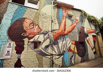 BERLIN, GERMANY - SEP 4: Girl falling down on street art composition by unknown artist at empty street on September 4 2015. Urban area of Berlin comprised 4 million people, 7th most populous in EU