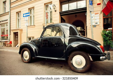 BERLIN, GERMANY - SEP 4: Vintage Fiat car parked on the empty street with restaurants on September 4, 2015. Urban area of Berlin comprised about 4 million people making it the 7th most populous in EU