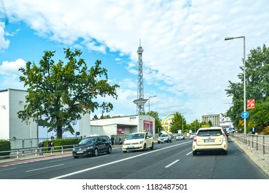 Berlin, Germany - September 1, 2018: Main street with various vehicles, which leads past the exhibition center. In the background you can see a landmark of the city, the radio tower (Funkturm).