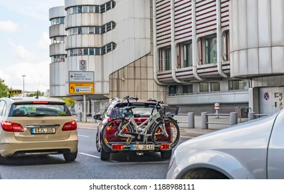 Berlin, Germany - September 1, 2018: Scene with a taxi and a car with a cycle carrier and two bikes in downtown Berlin.
