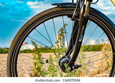 Berlin, Germany - September 12, 2018: View through the front wheel of a bicycle. In the background you can see a field and the unfocussed satellite town of Gropiusstadt in Berlin-Neukölln.