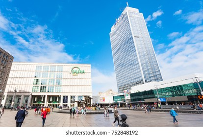 BERLIN, GERMANY - SEPTEMBER 13, 2017: people near shopping malls and hotel on Alexanderplatz square in Berlin city. Alexanderplatz is large public square and transport hub in central Mitte district