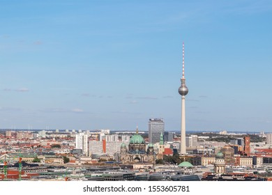 BERLIN, GERMANY - SEPTEMBER 14 2019: Cityscape with Berlin's iconic Television Tower at Alexanderplatz and the Berlin Cathedral amidst rooftops.