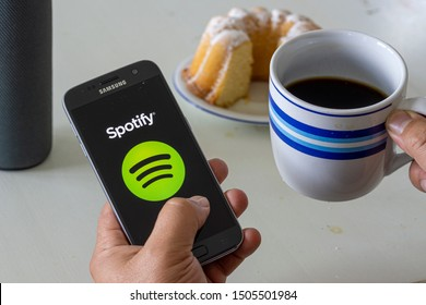 BERLIN, GERMANY - SEPTEMBER 15, 2019: Man holding a Samsung phone, opening spotify app, Spotify is a music service that offers legal streaming music.