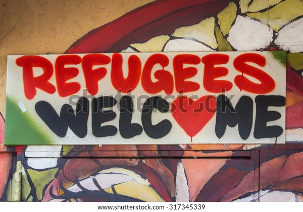 """Berlin, Germany , September 16, 2015: Graffiti with the political slogan """"Refugees Welcome"""", Berlin."""