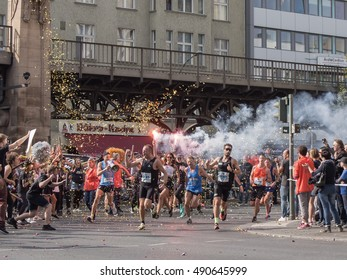 BERLIN, GERMANY - SEPTEMBER 25, 2016: Spectator With A Torch And Runners At Berlin Marathon 2016