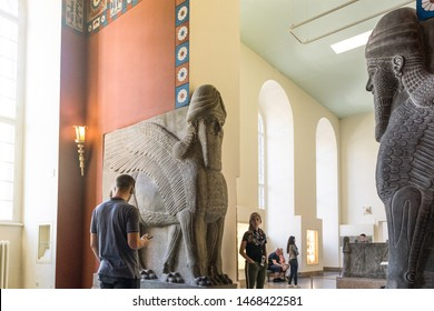 BERLIN, GERMANY - SEPTEMBER 26, 2018: Bright picture of visitors looking at statue exhibitions of Lamassu, an Assyrian protective deity, in the Assyrian chamber, at the Pergamon history museum