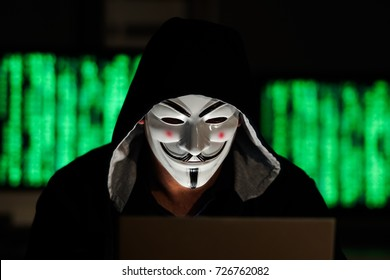 Berlin, Germany - September 27, 2017: Hacker man wearing a hood and an Anonymous Guy Fawkes mask at computer