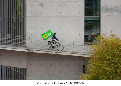 """BERLIN / GERMANY - SEPTEMBER 5th, 2009: Bicycle rider carrying the flag of the German Green Party (""""Die Gruenen"""") in front of Paul-Loebe-Haus in Berlin's government district"""