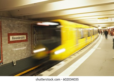 Berlin , Germany-01 March, 2017:yellow train in motion at underground (U-Bahn) train station Alexanderplatz. Alexanderplatz sign on the wall.