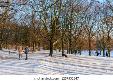 BERLIN, GERMANY-DECEMBER 2017 : Outdoor winter scenery of family and couple enjoy snowy landscape of Volkspark Rehberge, Goethe Park and Rathenaubrunnen in Wedding district, in Berlin, Germany.