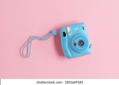 BERLIN, GRMANY - OCTOBER 19, 2020: The pink Fujifilm Instax mini 11 instant camera on background. High quality photo
