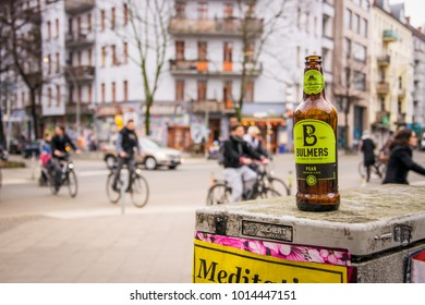 BERLIN - JANUARY 27, 2018: Group of cyclists pass empty bottle of Bulmers pear cider left behind in former East Berlin district of Friedrichshain-Kreuzberg.