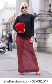 BERLIN - July 10, 2015: Stylish woman wearing a black pullover, red skirt and shoes and carrying a red bag in front of the Kronzprinzenpalais. Berlin Fashion Week Spring / Summer 2016