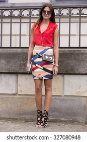 BERLIN - July 10, 2015: Young stylish woman wearing a red sleeveless shirt and colourful skirt after a fashion show. Berlin Fashion Week Spring / Summer 2016