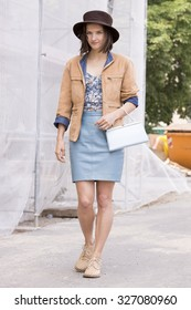 BERLIN - July 10, 2015: Young stylish woman wearing a pastel blue short dress, suede jacket and a brown hat after a show at the Kronzprinzenpalais. Berlin Fashion Week Spring / Summer 2016