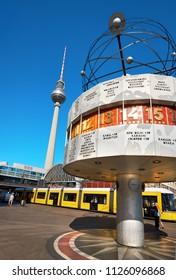 BERLIN - JULY 3, 2018: Berlin's Alexanderplatz, Weltzeituhr (World Time Clock), yellow tram and TV Tower. Alexanderplatz is the central transportation hub of Berlin.