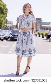 BERLIN - July 7, 2015: Stylish woman wearing T-shirt and skirt with blue prints in front of Brandenburg Gate. Berlin Fashion Week Spring / Summer 2016