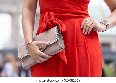 BERLIN - July 8, 2015: Stylish woman wearing a red jumpsuit and carrying a bag with rivets. Berlin Fashion Week Spring / Summer 2016