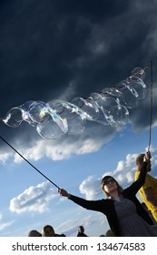 BERLIN - JUN 10: A young woman making giant soap bubbles on an early summer day at Mauerpark, with the park's crowd all around on June 10 2012 in Berlin, Germany.