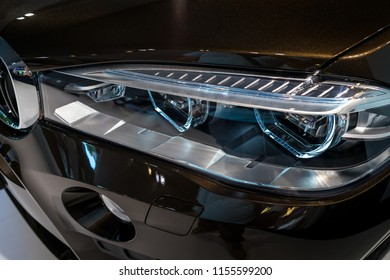 BERLIN - JUNE 09, 2018: Showroom. Headlamp of a mid-size luxury crossover SUV BMW X6 M. Close-up.