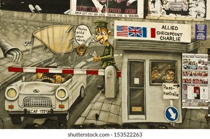 "BERLIN - JUNE 13: artwork depicting ""Checkpoint Charlie"" on the Berlin Wall on June 13, 2013 in Berlin, Germany. The Berlin Wall divided Berlin between 1961 and 1989."