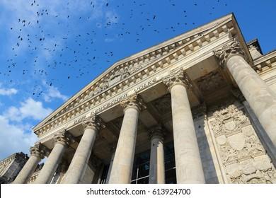 Berlin landmark - Reichstag government building. Ominous black birds.