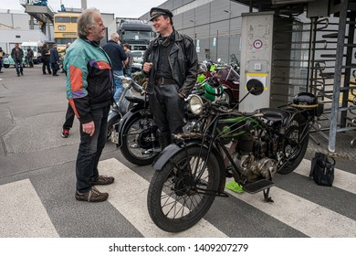 BERLIN - MAY 11, 2019: The owner of a motorcycle D-Rad R-O / 4, dressed in the style of the 20s, talking to a visitor. 32th Berlin-Brandenburg Oldtimer Day.