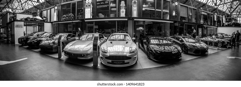 BERLIN - MAY 11, 2019: Panoramic view of the garage of Classic Remise Berlin, modern sports cars, repair and service offices - venue of 32th Berlin-Brandenburg Oldtimer Day. Black and white.