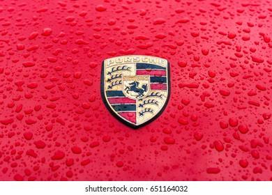 "BERLIN - MAY 13, 2017: Hood emblem of sports car Porsche in raindrops on the red background. Exhibition ""Oldtimertage Berlin-Brandenburg""."