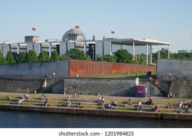 BERLIN, MITTE / GERMANY - MAI 13 2018: People sitting and walking at the river next to governmental buildings.