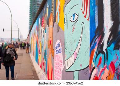 BERLIN - NOV 15, 2014: Unidentified people walking and looking at the Berlin Wall at East Side Gallery.