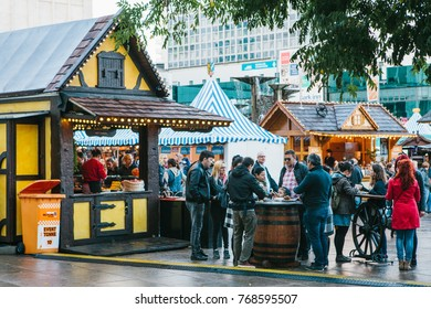 Berlin, October 03, 2017: Celebrating the Oktoberfest. People walk on the street market on the famous Alexanderplatz square. Many stalls with souvenirs and food nearby. People eat traditional food.