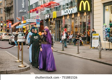 Berlin, October 1, 2017: Group of positive women - Arab refugees in national costumes with an expensive phone walking through the streets of Berlin