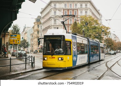 Berlin, October 2, 2017: City public transport in Germany. Beautiful black and yellow train stopped at stop on the background of an old building.