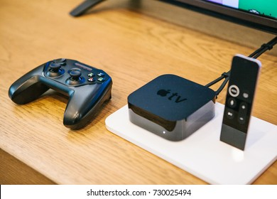 Berlin, October 2, 2017: presentation of new Apple products in the official Apple store. Modern advanced block Apple TV with a joystick and control panel lie on the table.