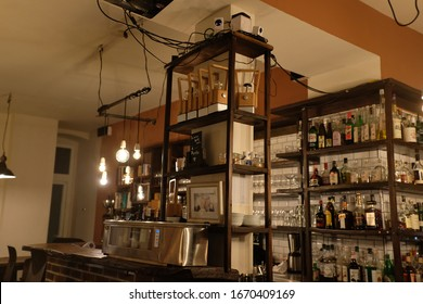 Berlin, Prenzlauer Berg / Germany - February 14 2020: Quaint Restaurant Bar with Wooden Shelves, Brick Counter, Lamps, Spirits, Alcohol, Whiskey, Exposed Lightbulbs. Cosy, Vintage Hipster Retro Style.