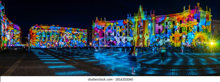 BERLIN - SEPTEMBER 15, 2020: The Bebelplatz, Hotel de Rome (left) and Humboldt University law faculty (right) in brightly colored illuminations. Lens flare. Panoramic view. Festival of lights 2020.