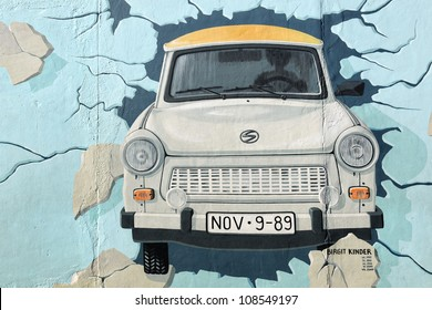 BERLIN - SEPTEMBER 3: Mural of Trabant car breaking through Berlin Wall at East Side Gallery September 3, 2011 in Berlin