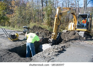 Berlin, VT, USA - October 2, 2013: On a warm autumn morning, members of the Berlin, Vermont road crew cut a trench in Paine Turnpike Rd in order to install a new culvert.