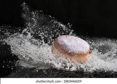 Berliner donut with jam stuffed falls into flour.