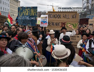 Berlin/Germany - 10/12/2019: Demostration and protest against President Moreno's politics in Ecuador, crowd of people in traditional clothes showing banners and posters while playing music