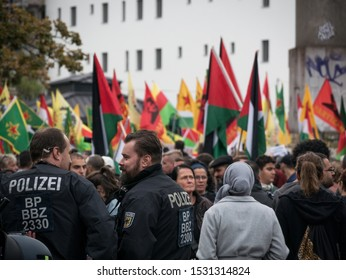 Berlin/Germany - 10/12/2019: Plenty policemen and police cars at demonstration and protest against Turkish politics and offensive in North Syria/Kurdistan, Kurdish and YPG flags in the background