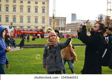 Berlin/Germany - 29 October,2019:Girl trying to catch a soap bubble in the center of Berlin
