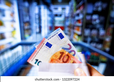 Berlin,Germany, European Union 02/25/2019 Cash euro money in envelope with shopping supermarket cart. Buying groceries concept. Colorful soft bouquet. Financial living, inflation costs, market concept