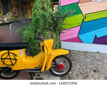 Berlin/Germany - July 31,2018: Yellow motorbike with anarchy sign on in front of a painted wall with another wall with a blonde woman illustration on it.