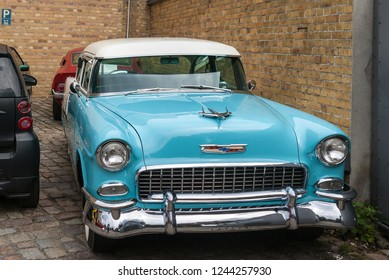 Berlin/Germany-July 24, 2018 Classic American Car 1955 Chevrolet Bel Air hardtop , blue and white color against a brick wall.